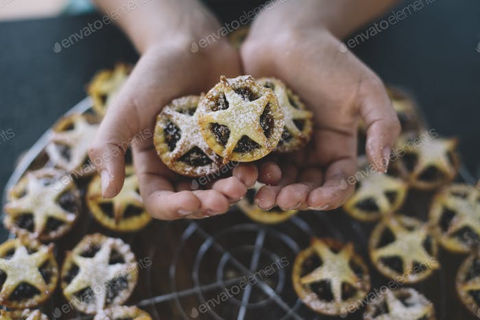 Christmas baking, a child's hands holding freshly baked mini mincemeat tarts