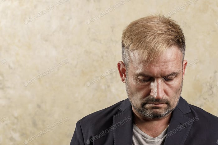 Caucasian middle-aged pensive man. Lowered gaze. Not looking at the camera.