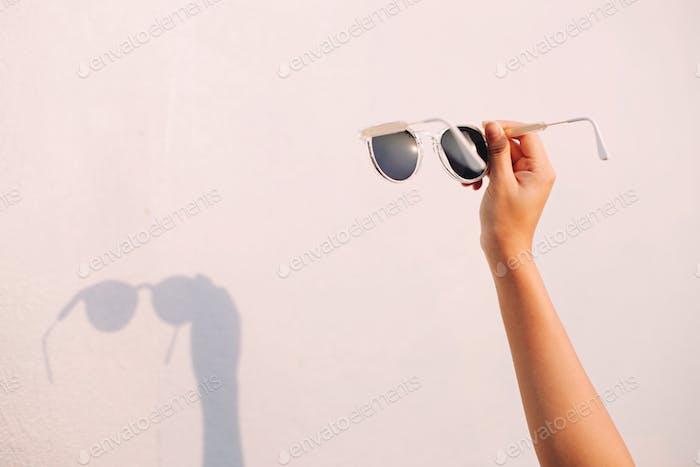 Concepto de verano, gafas de sol de mano