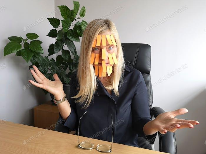 Müde und deprimierte reife Geschäftsfrau mit vielen gelben Memo-Notizen im Gesicht, Nahaufnahmeporträt.