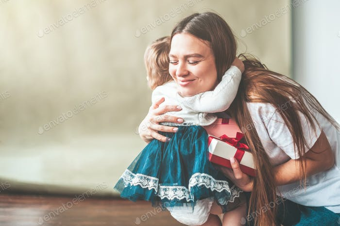 Mom hugs her little daughter and is happy with the gift.