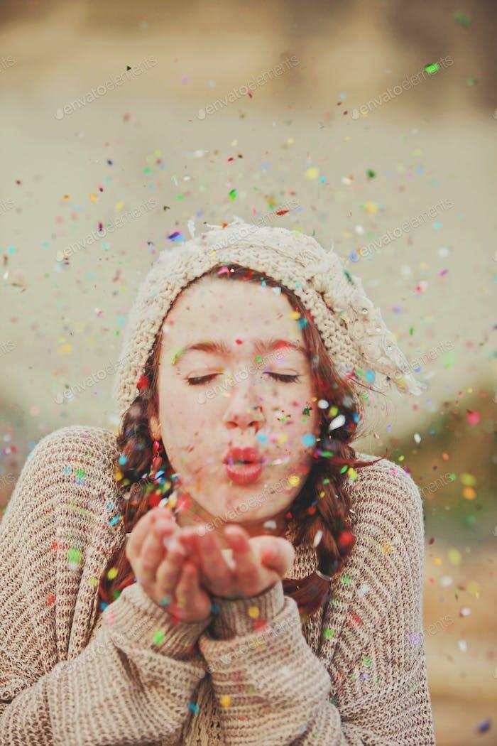 teen girl blowing glitter