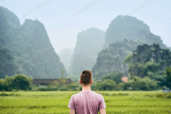 Traveler in Vietnam. Rear view of young man against karst hills near Tam Coc in Ninh Binh province.