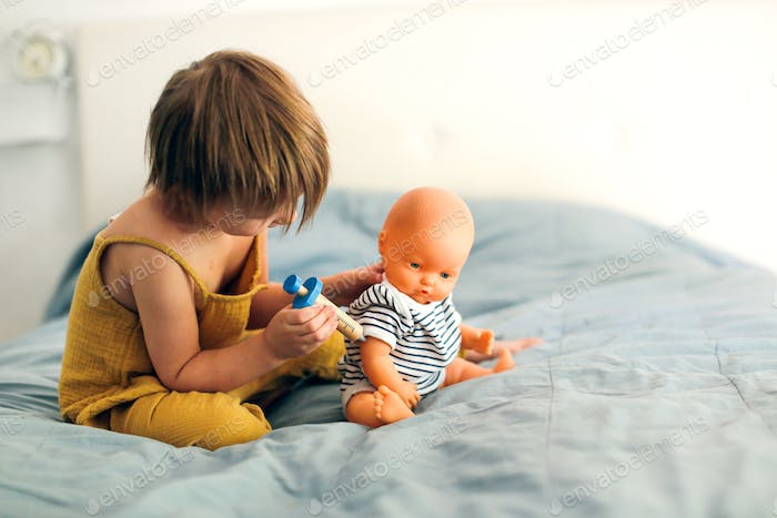 Girl child makes an injection with a wooden syringe to a doll, vaccination