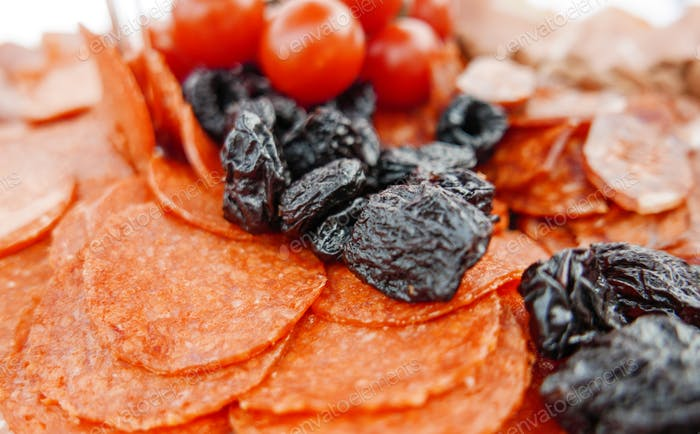 Cold cuts at a banquet. Dryied plum, figs, food, eating, closeup, salami.