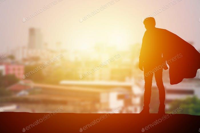 Silhouette von intelligenten erfolgreichen Männchen Mann tragen wie Superheld auf der Oberseite des Gebäudes über