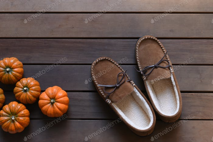 Slippers and pumpkins on a wooden floor