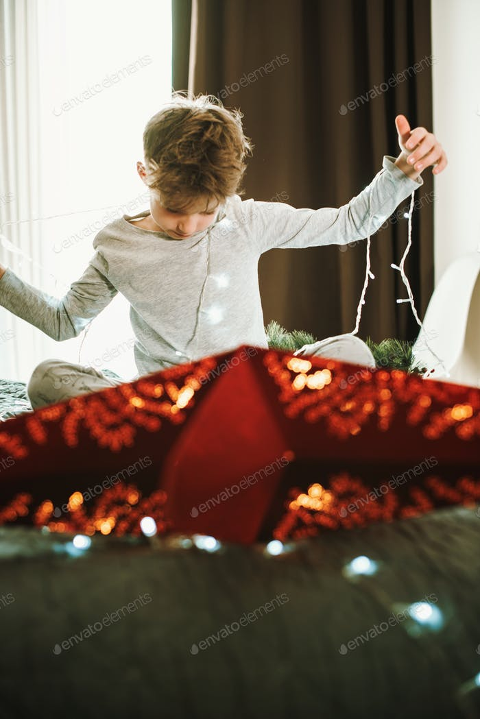 Boy decorating home for Christmas with red star. Magic of christmas
