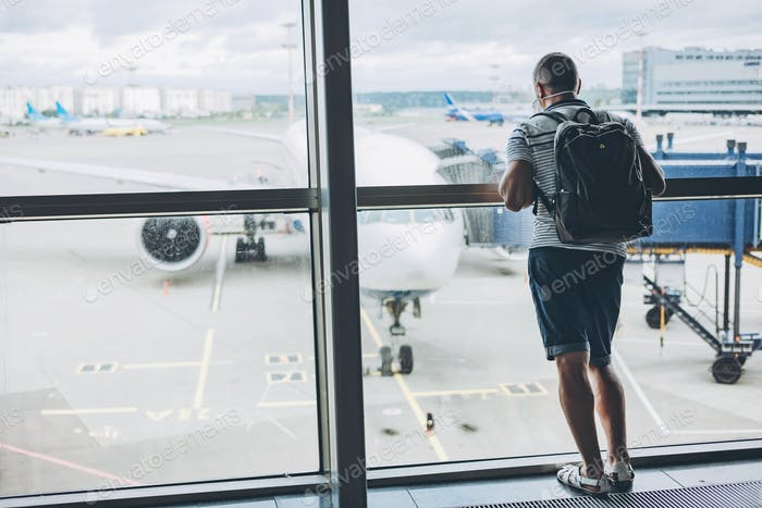 Man in protective mask with backpack at airport terminal waiting for departure looking out window