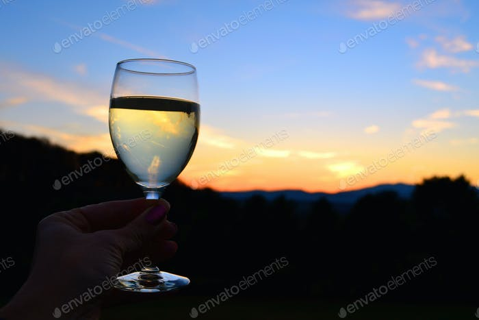 Toasting the sunset over the mountains with a glass of white wine. Seize the Day! Carpe Diem!