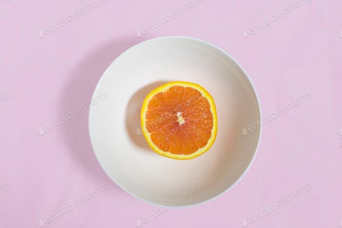 Flatlay over head shot of half of a blood orange in crisp white porcelain bowl on a soft pastel pink