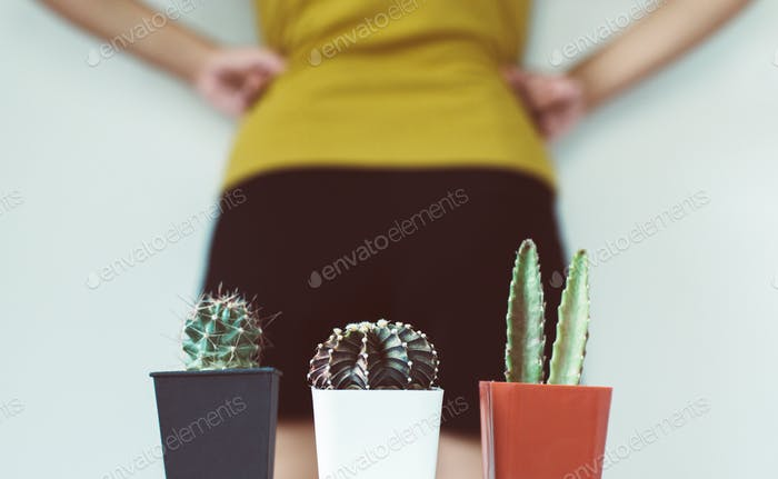 Blurred woman standing on white background with cactus and suffering from hemorrhoids