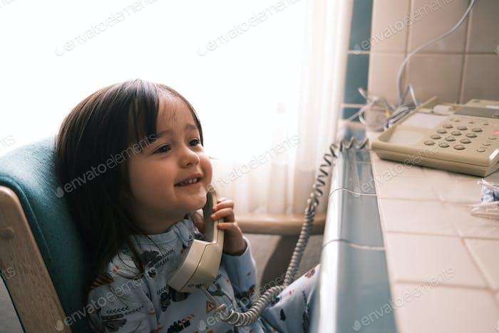 Niña feliz hablando en un teléfono fijo