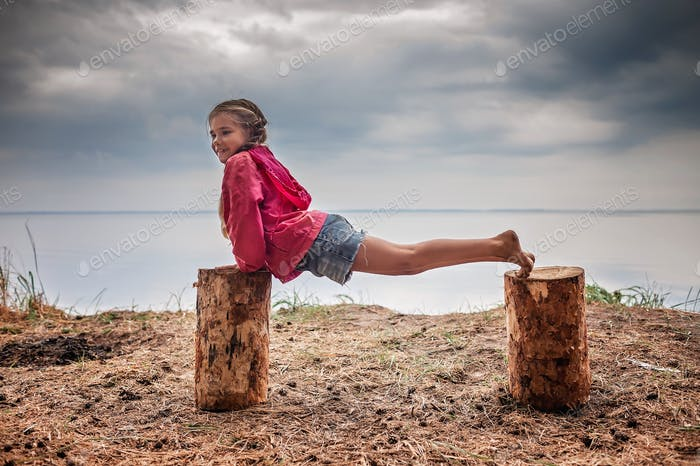 Self-isolation and fitness in wild nature. Slim girl doing exercises using stubs as sport equipment