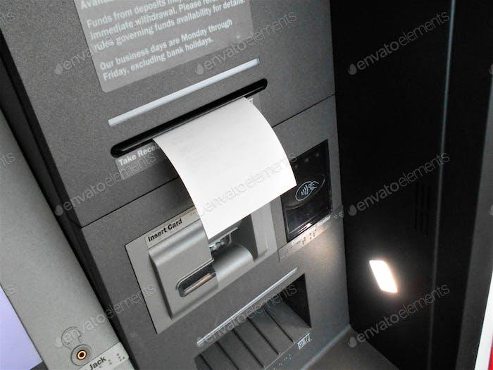 Bankgeschäfte über einen Geldautomaten! Die Quittung für meine Transaktion wird durch den ATM-Slot ausgeworfen.