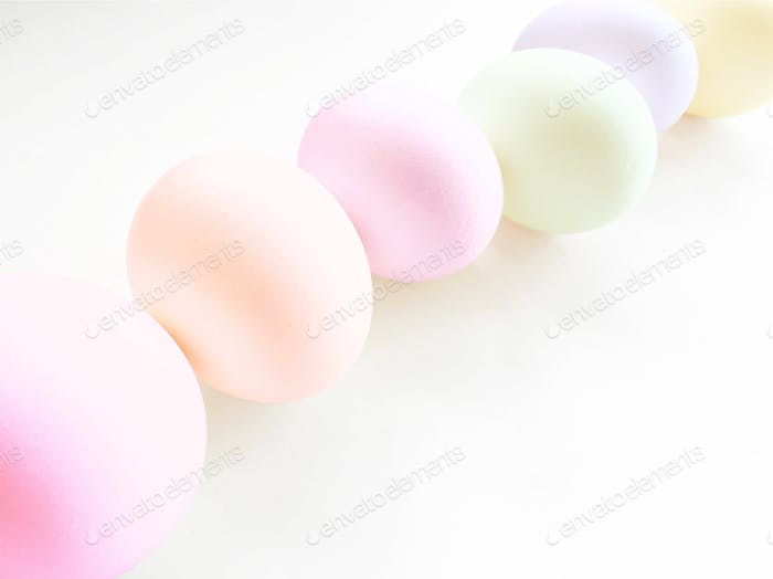 Staggered diagonal row of pastel painted Easter eggs on a white background.