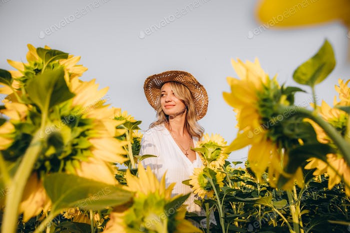 young girl in a straw hat and a sundress in a field of sunflower seeds