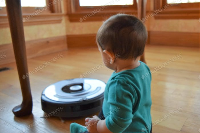 Baby watching a robotic vacuum while sitting underneath the kitchen table