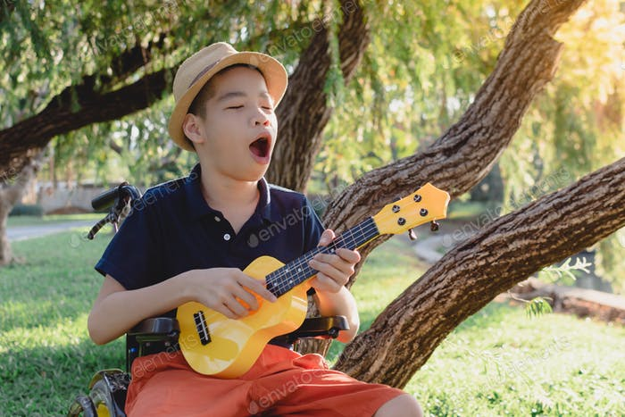 Asian special child on wheelchair is playing ukulele happily on the city park with nature light