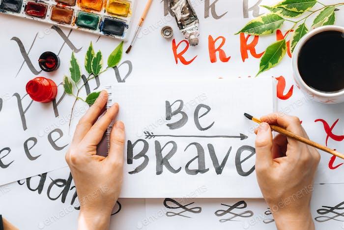 Motivationsbuchstaben Wörter Zitat BE BRAVE geschrieben mit schwarzem Pinsel