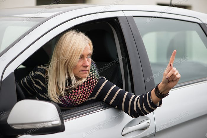 An angry mature woman is driving a car