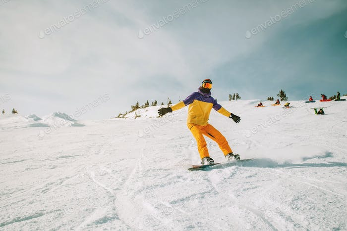 Male snowboarder motion shot on a slope sunny day
