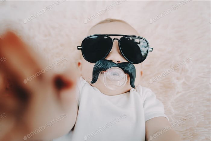Funny baby boy in aviator sunglasses with mustache nipple