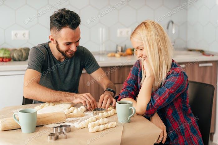 Jóvenes felices riéndose cocinando en la cocina