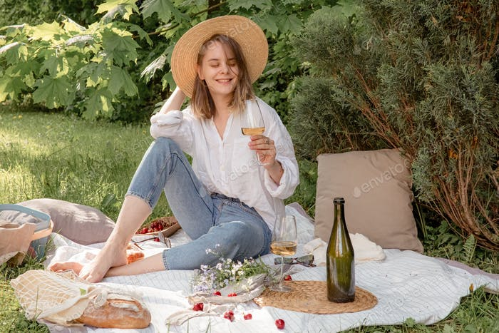 Woman on a picnic drinking wine and smiling