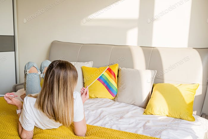 Woman with rainbow flag on bed. Lesbian celebrating pride month during Covid-19 Coronavirus pandemic