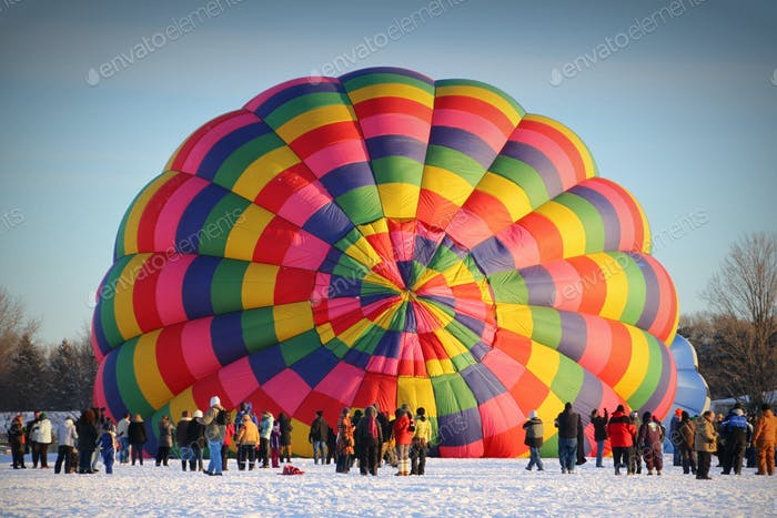 View from afar of a colorful hot air balloon being inflated with people watching in winter.