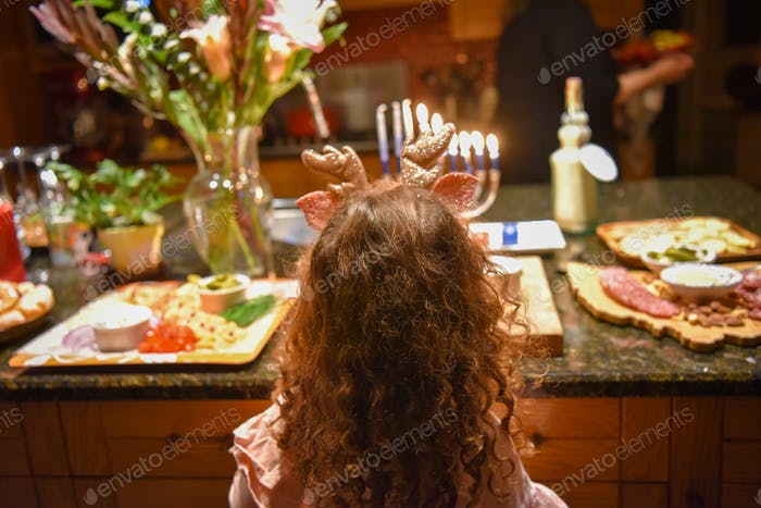 A young girl with reindeer ears stands in front of a counter of appetizers in celebrating Hanukkah.