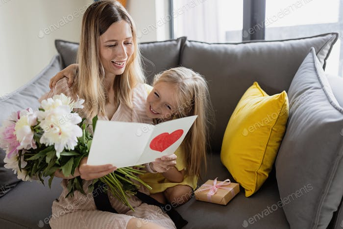 Happy caucasian mommy and daughter sitting on couch and celebrating mother's day at home