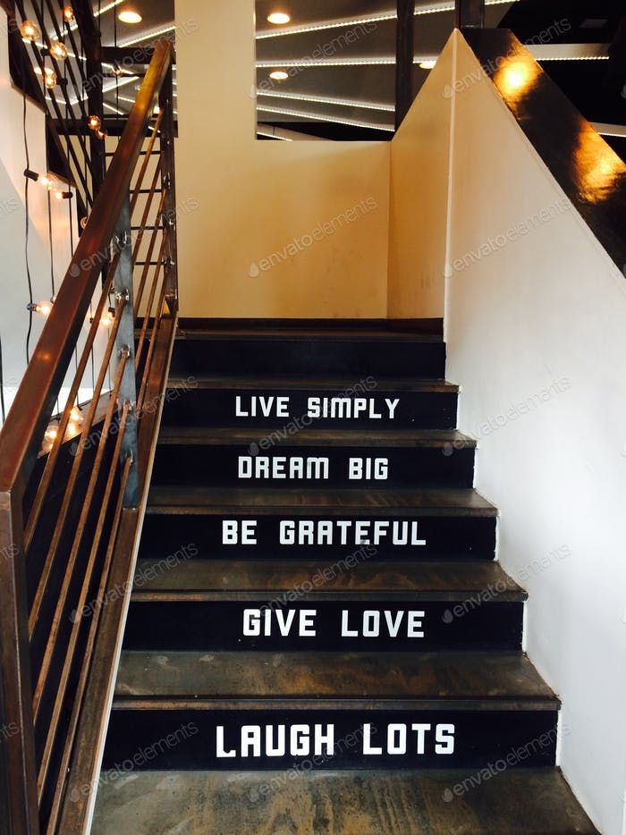 Inspirational quote. Words on stairs at modern restaurant