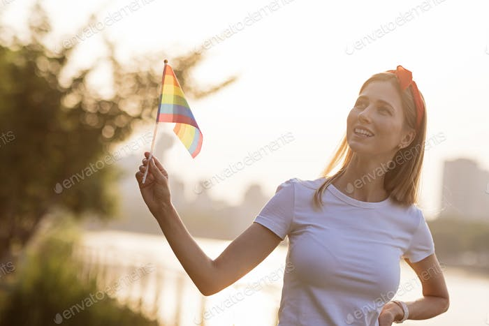 Woman hand holding lgbtq rainbow flag outdoors on sunset. Mockup for pride parade