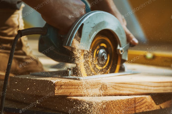 Close-up of a carpenter using a circular saw to cut a large board of wood a new home constructiion p