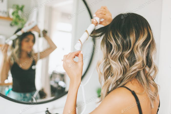 A woman curling her hair in the bathroom mirror.