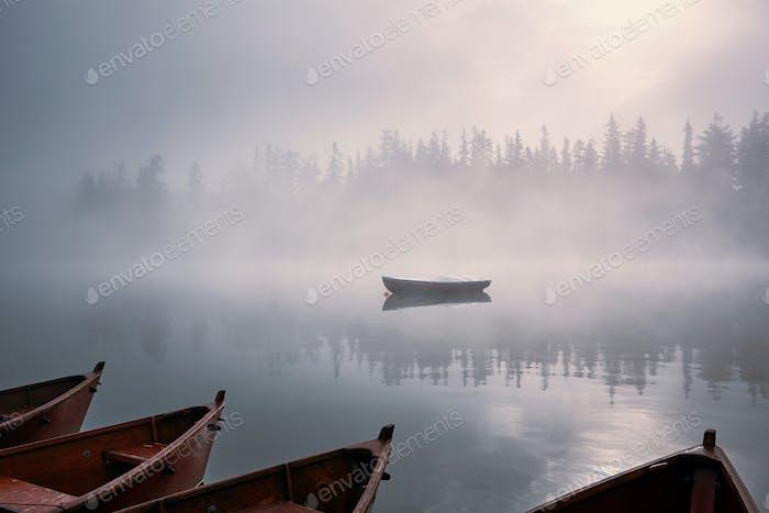 Boats on mountain lake in mysterious fog. Strbske pleso in High Tatras, Slovakia.