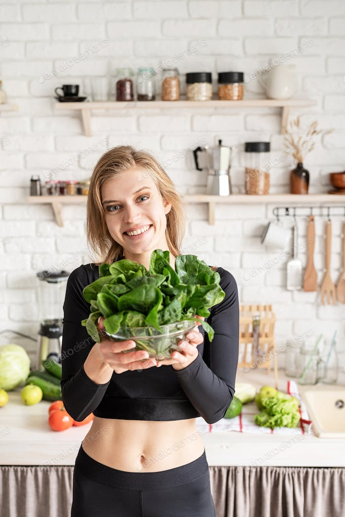 healthy eating, diet and cooking concept. Young blond smiling woman holding a bowl of fresh spinach