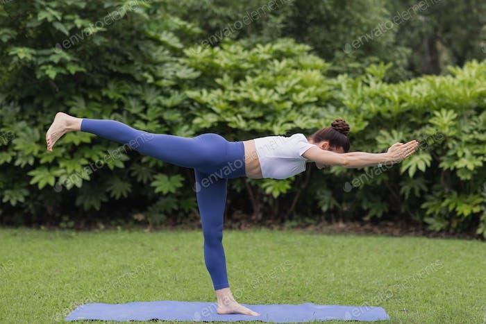 glücklicher junger sportlicher Yoga-Coach-Lehrer, der morgens auf Matte liegt und im Sommerpark draußen trainiert