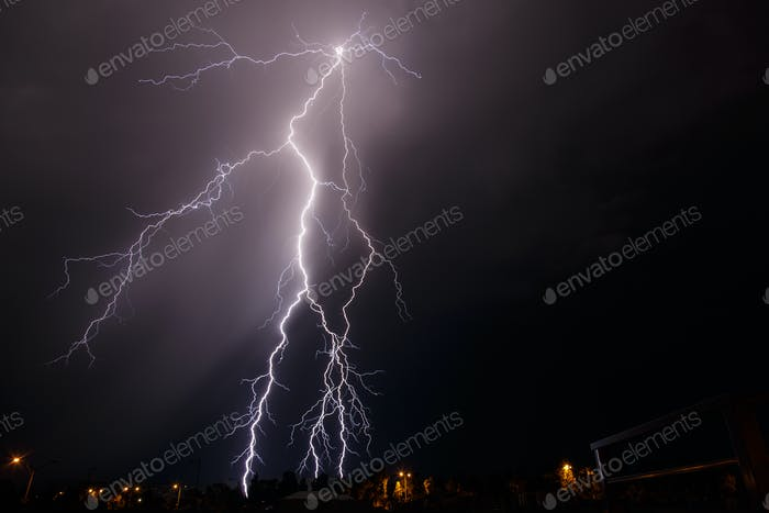Branched lightning strike behind houses lights up the night sky