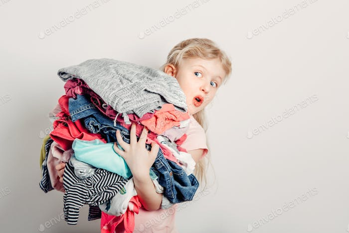 Cute funny surprised girl holding pile of dirty clothes ready for washing, organising. Home chores.