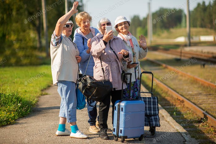 senior women take a self-portrait on platform waiting for train to travel during COVID-19 pandemic