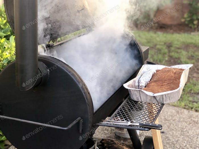 Smoker emitting smoke with large brisket ready to be smoked