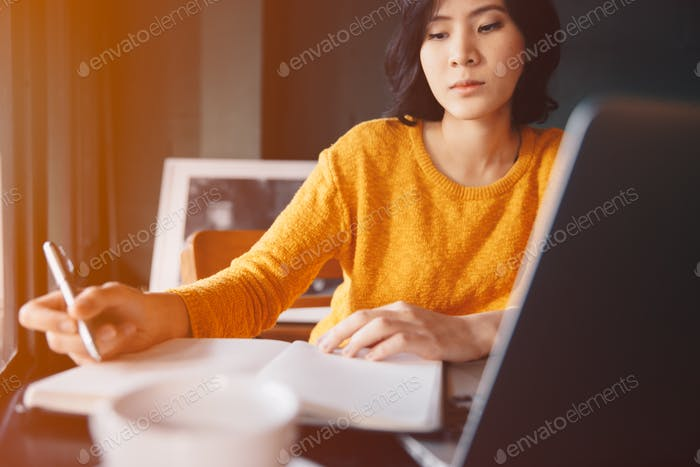 Young business woman in yellow dress sitting at table in cafe and writing in notebook.
