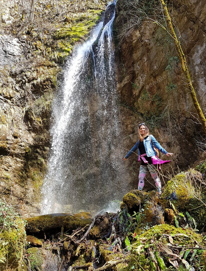A yong millenial woman standing under a waterfall and spreading her arms.