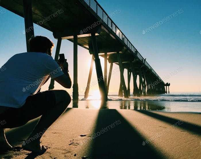 Cool dude taking an epic photo of the pier.