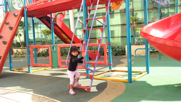 Daughter playing in the children play area outside home