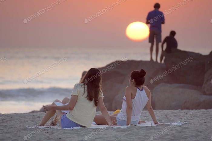 Candid people at the beach during sunset