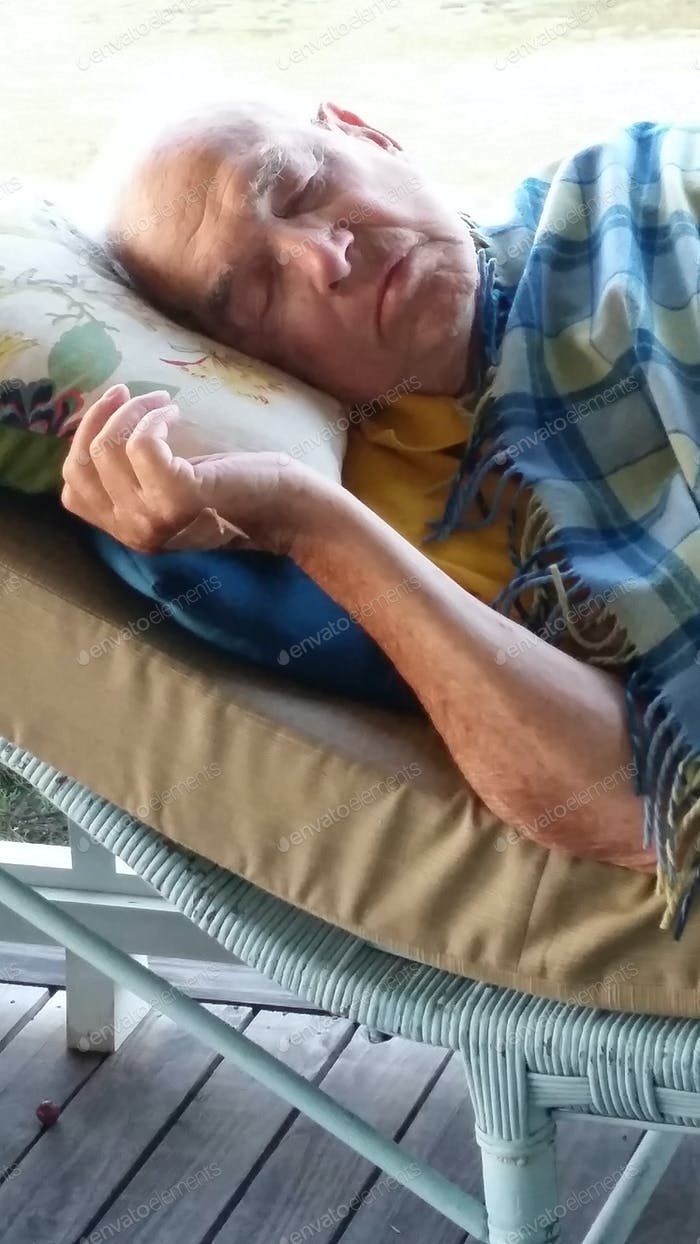 Пожилой джентльмен дремлет на крыльце